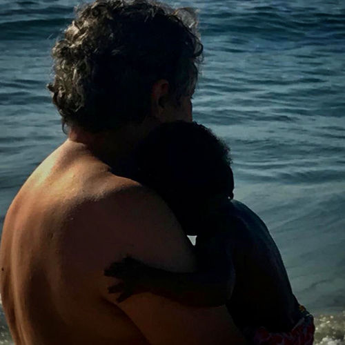 Rear view of shirtless man sitting at sea shore