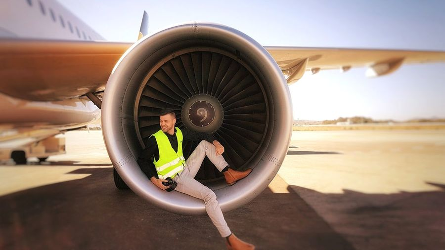 Male worker sitting on airplane engine at runway