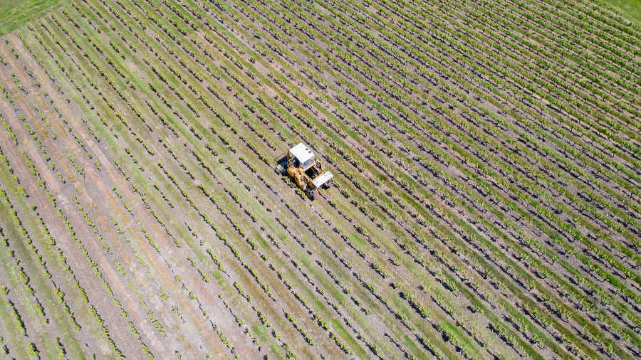 Aerial View Of Agricultural Machinery Working On Farm