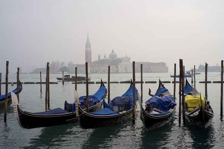 Gondolas moored in grand canal against san giorgio maggiore during foggy weather