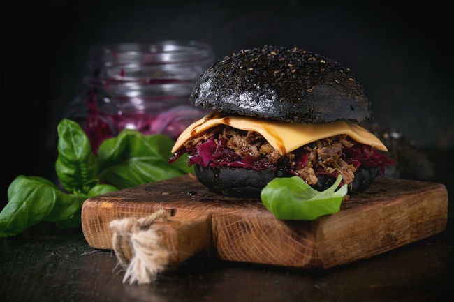 Black burger with stews, cheese, red cabbage and balsamic sauce served on small wooden chopping board with fresh basil over wooden table with black background. Basil Black Background Burger Dark Fast Food Food And Drink Herbs Homemade Food Pork Stew Black Burger Black Food Cabbage Cheese Chopping Board Hamburger Junk Food Kitchen Meat Modern Food Purple Sauce