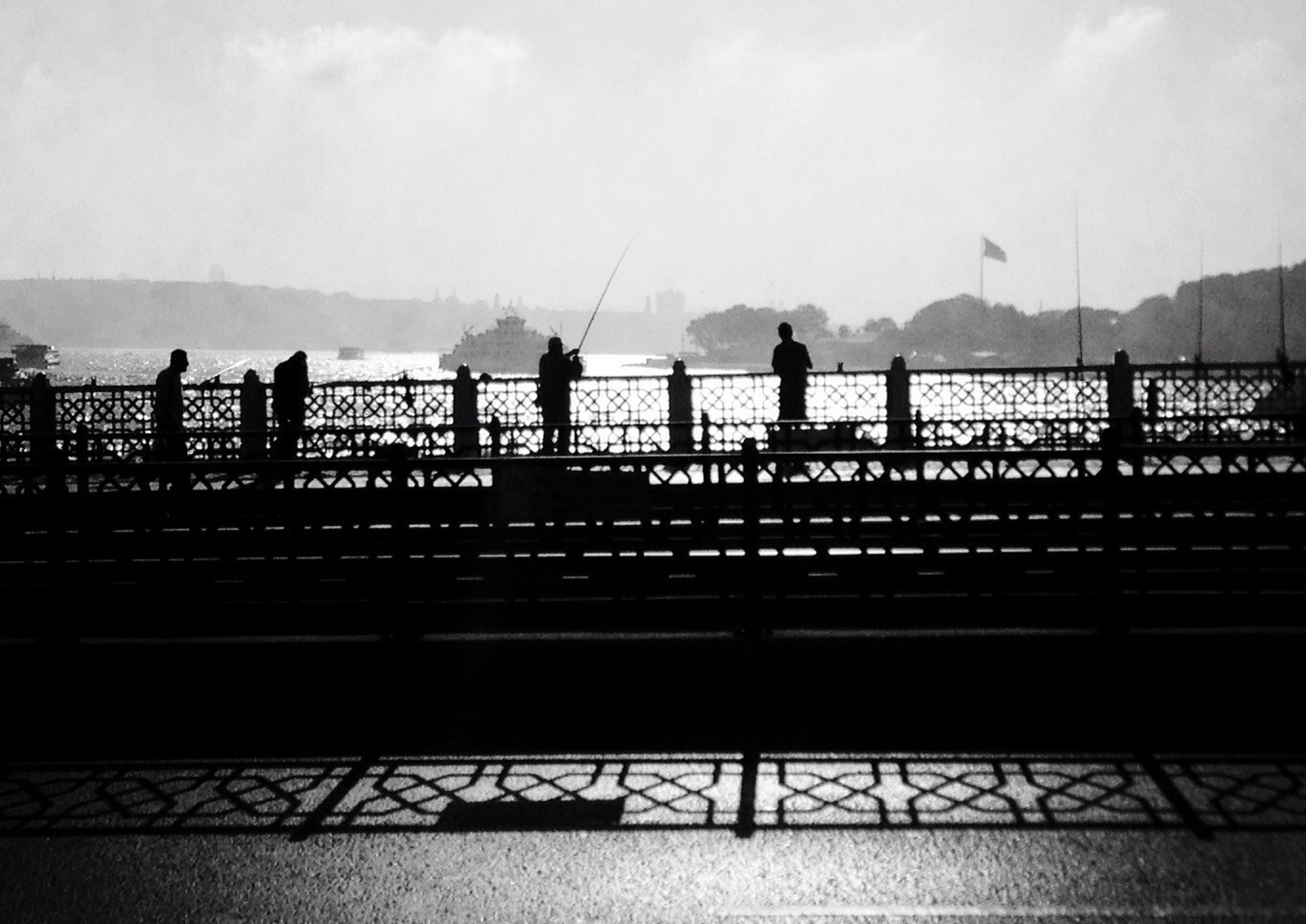 railing, lifestyles, men, leisure activity, silhouette, person, walking, sky, bridge - man made structure, full length, connection, medium group of people, standing, togetherness, water, rear view