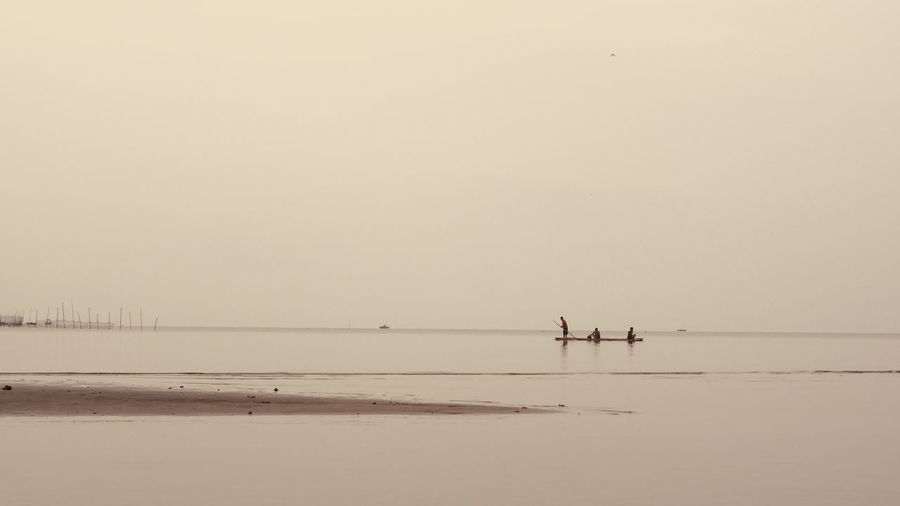 Silhouette People Rowing On Beach Against Sky
