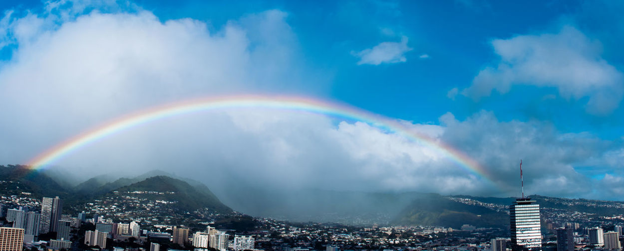 Panoramic View Of Rainbow Over Cityscape Against Sky