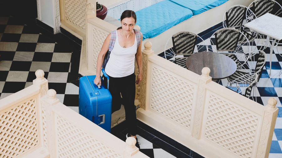 High angle view of woman carrying suitcase at hotel