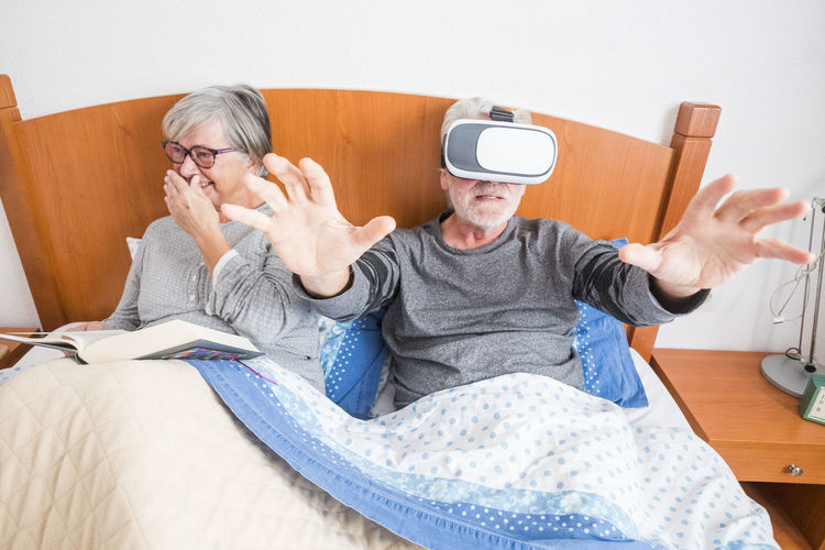 Man Gesturing While Using Virtual Reality Simulator With Woman On Bed