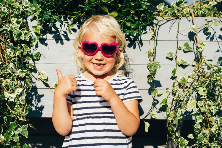 Portrait of woman wearing sunglasses against plants