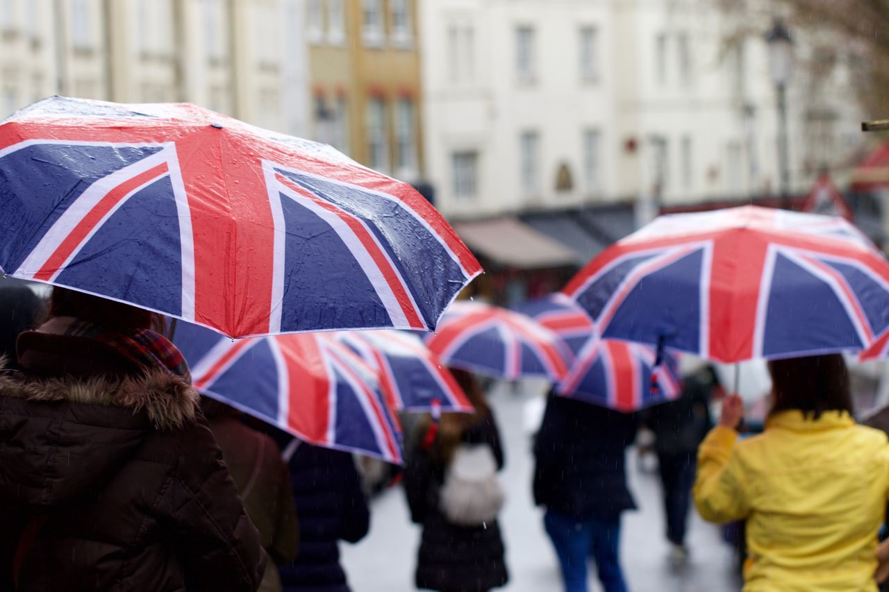 Rear view of people with british flag walking on city street during rainy season