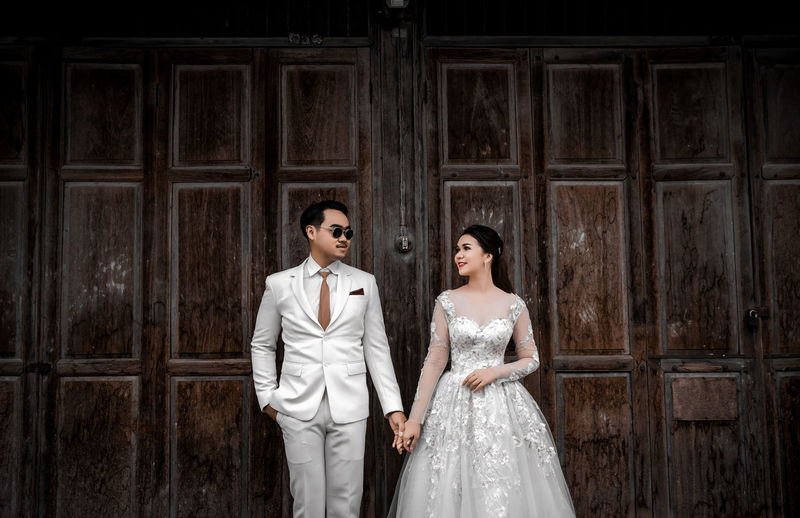Newlywed couple holding hands while standing against wall