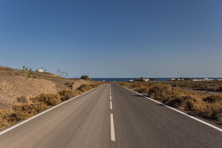 Empty road towards the sea in fuerteventura, canary islands