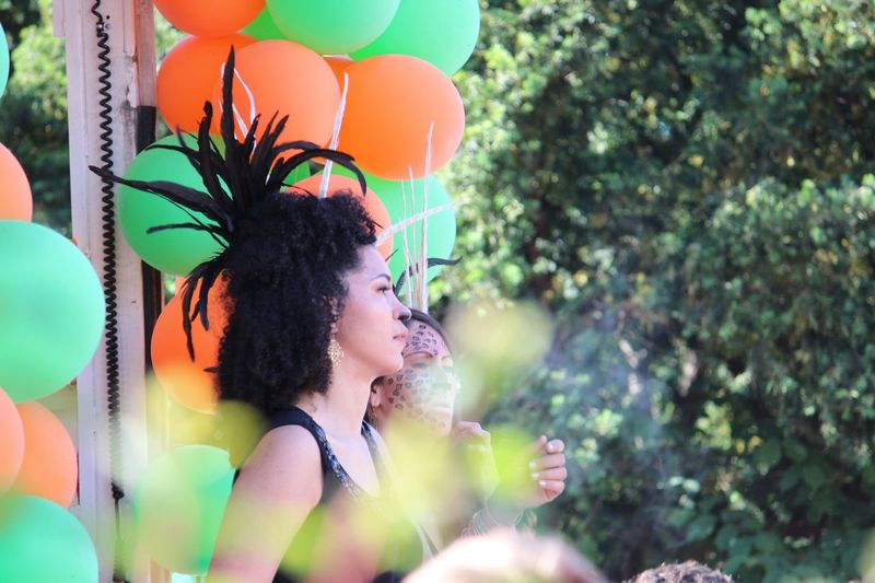 Balloon Carnival Procession Close Up Coloured Balloons Feathered Headdress Real People Smiling Tree Two People Young Women