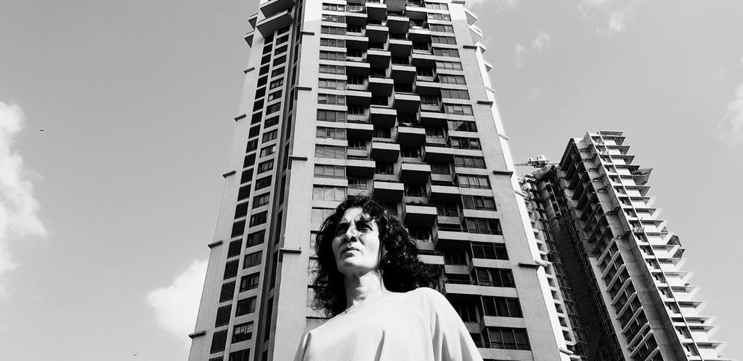 Low angle view of woman looking at building against sky