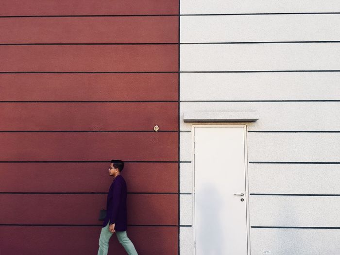 Side view man walking by wall outdoors