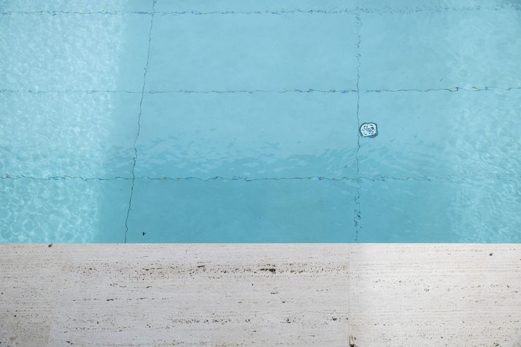 Close-up of blue wall by swimming pool