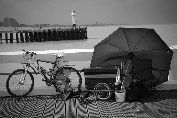 Bicycle with umbrella and chair on bridge against lighthouse