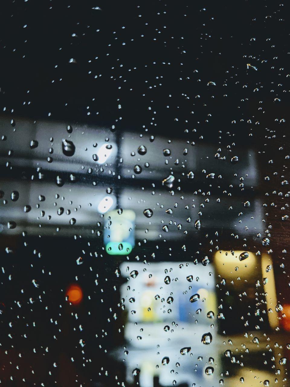 FULL FRAME SHOT OF WET GLASS WINDOW WITH RAIN DROPS