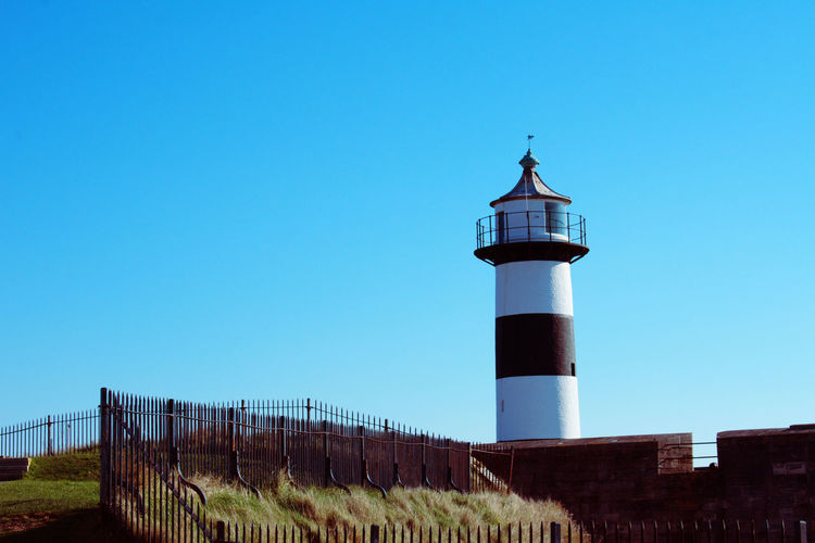 Lighthouse against clear blue sky