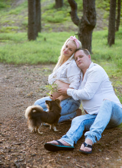 Full length of pregnant couple with dog against tree trunk