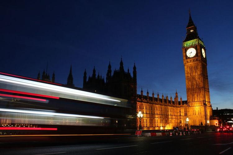 Blurred motion of bus leading towards illuminated big ben night