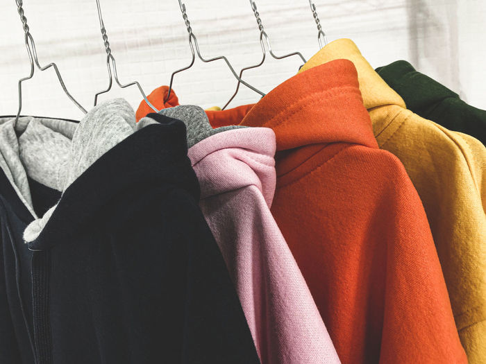 Close-up of multi colored hoodie hanging for sale at market