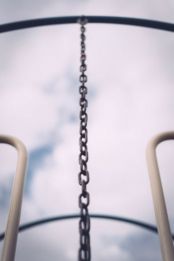 Low angle view of metallic chain hanging on outdoor play equipment at playground