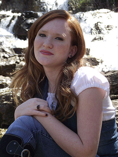 Portrait of a young woman sitting near a waterfall. One Person Young Woman Female Denim Casual Clothing Long Hair Redhead Red Hair Outdoors Nature Water Waterfall Sitting Posing Model Portrait Beautiful Woman Looking At Camera Front View Close-up