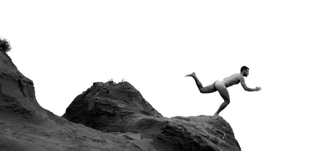 Full length of shirtless man jumping on rock against clear sky