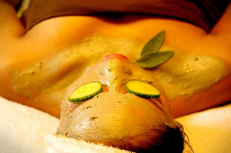 Close-up of woman with facial mask on bed at spa