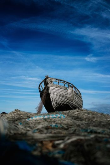 Low angle view of abandoned boat on beach against blue sky