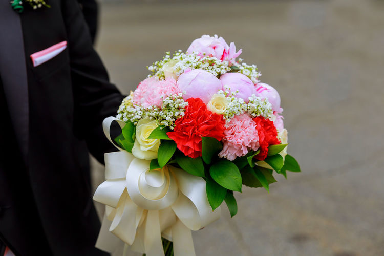 Midsection of groom holding colorful bouquet on walkway