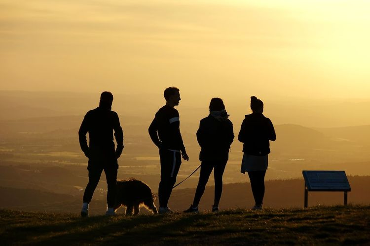 Silhouette people walking on land against sky during sunset
