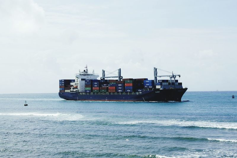 Cargo boat sailing on sea against sky