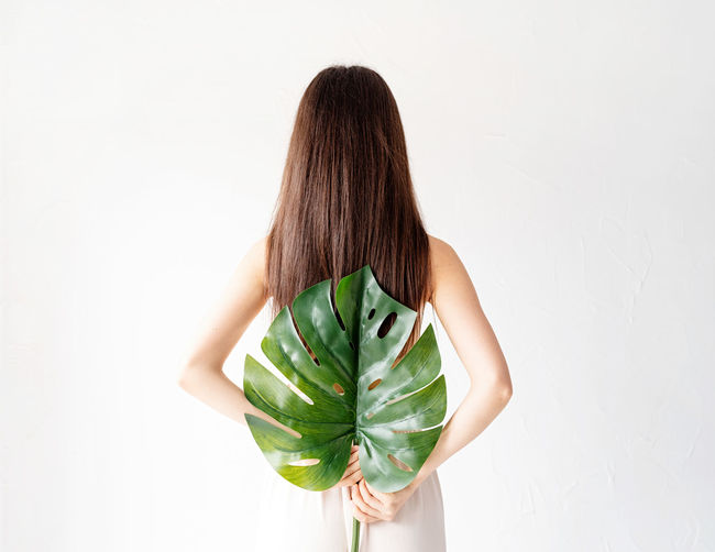 Rear view of woman holding leaf standing against white background