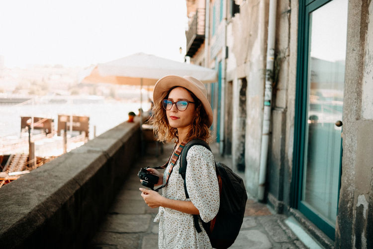 Portrait of woman standing on mobile phone in city
