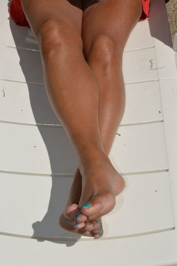 Low section of woman legs on tiled floor