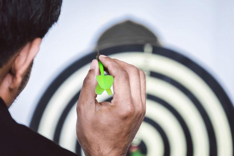 Cropped image of man holding dart