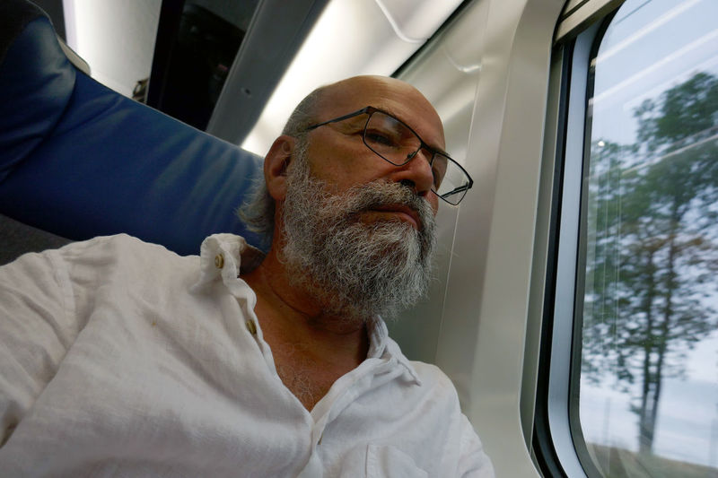 Casual Clothing Day Headshot Leisure Activity Lifestyles Portrait Journey On The Move Mode Of Transport Near Window On The Train Sitting Traveling Travel Relaxation Man Mature Man Beard Bearded