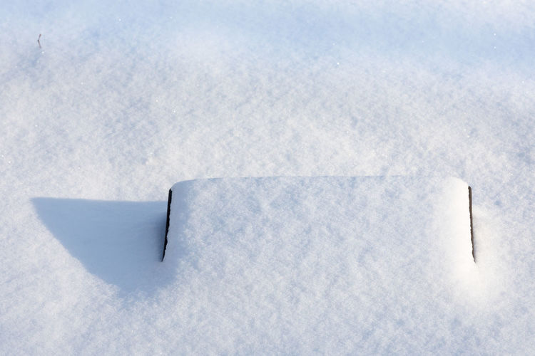 High Angle View Of Snow Covered Tombstone At Cemetery