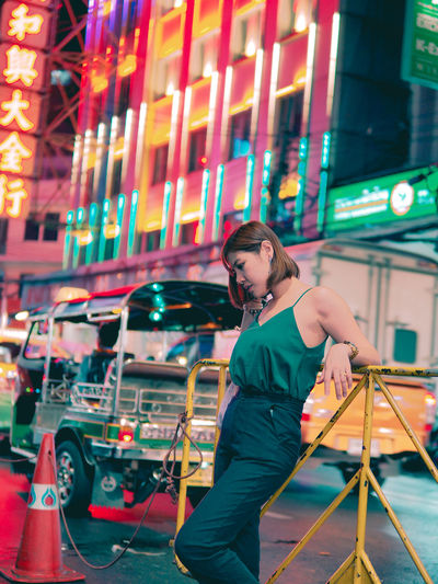 Full length of woman standing on illuminated city at night