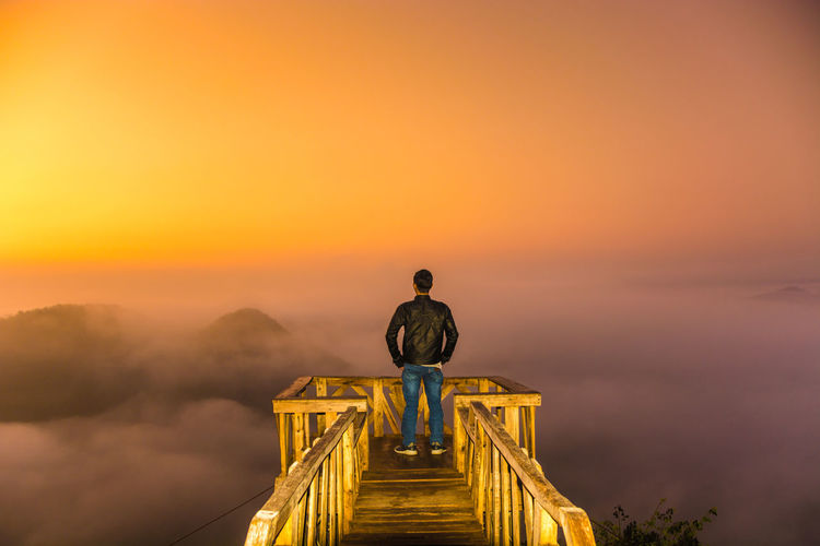 Man standing at observation point against sky during sunset
