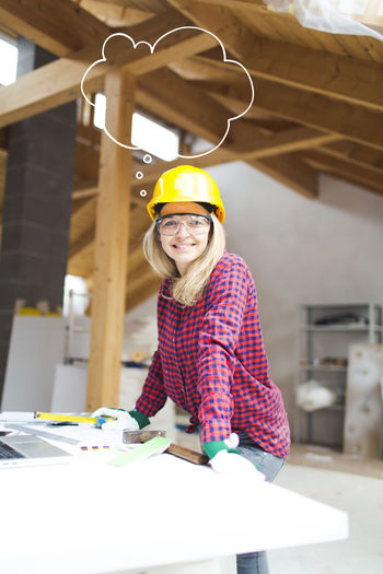 beautiful woman with yellow helmet is working in her loft Casual Clothing Cheerful Construction Site Craftsperson Happiness Hardhat  Headwear Indoors  Looking At Camera Manual Worker Occupation One Person Portrait Real People Skill  Small Business Smiling Standing Women Wood - Material Work Tool Workbench Working Workshop Young Women