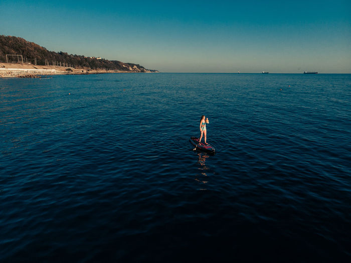 Full length of woman paddleboarding in sea