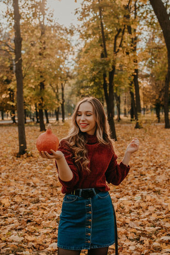 Portrait of smiling young woman standing in park during autumn