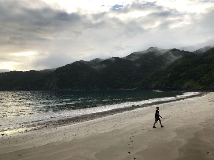 Man Walking At Beach Against Mountains During Sunset