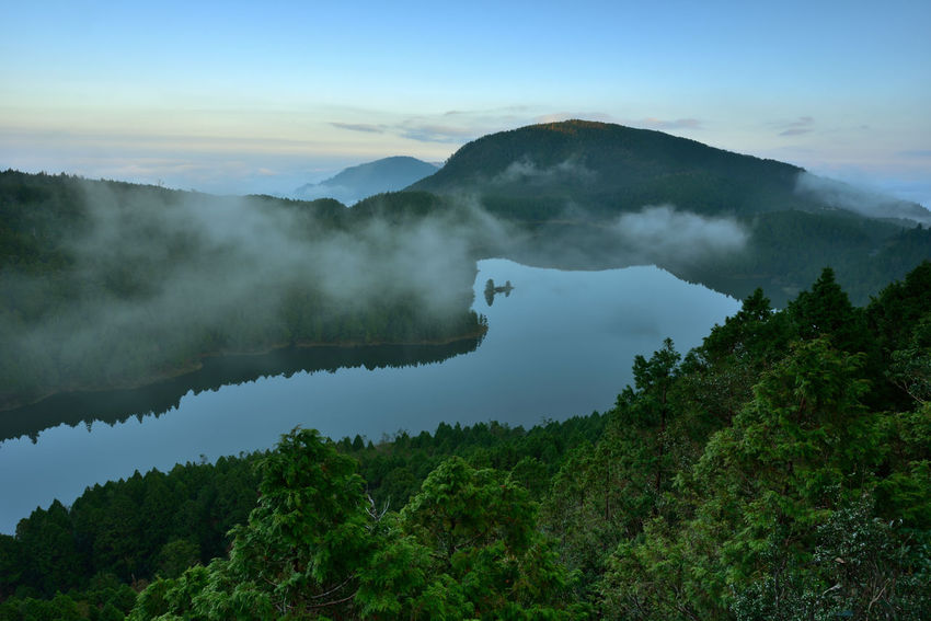 Beautiful natural landscape, the lake is quiet and picturesque. Broad Tranquil Lake Beauty In Nature Clouds Day Forest Green Lake Idyllic Lake Blue Landscape Mountain Mountain Lake Mountain Range Nature No People Non-urban Scene Outdoors Physical Geography Scenics Sky Smoke - Physical Structure Tranquil Scene Tranquility Travel Destinations Tree