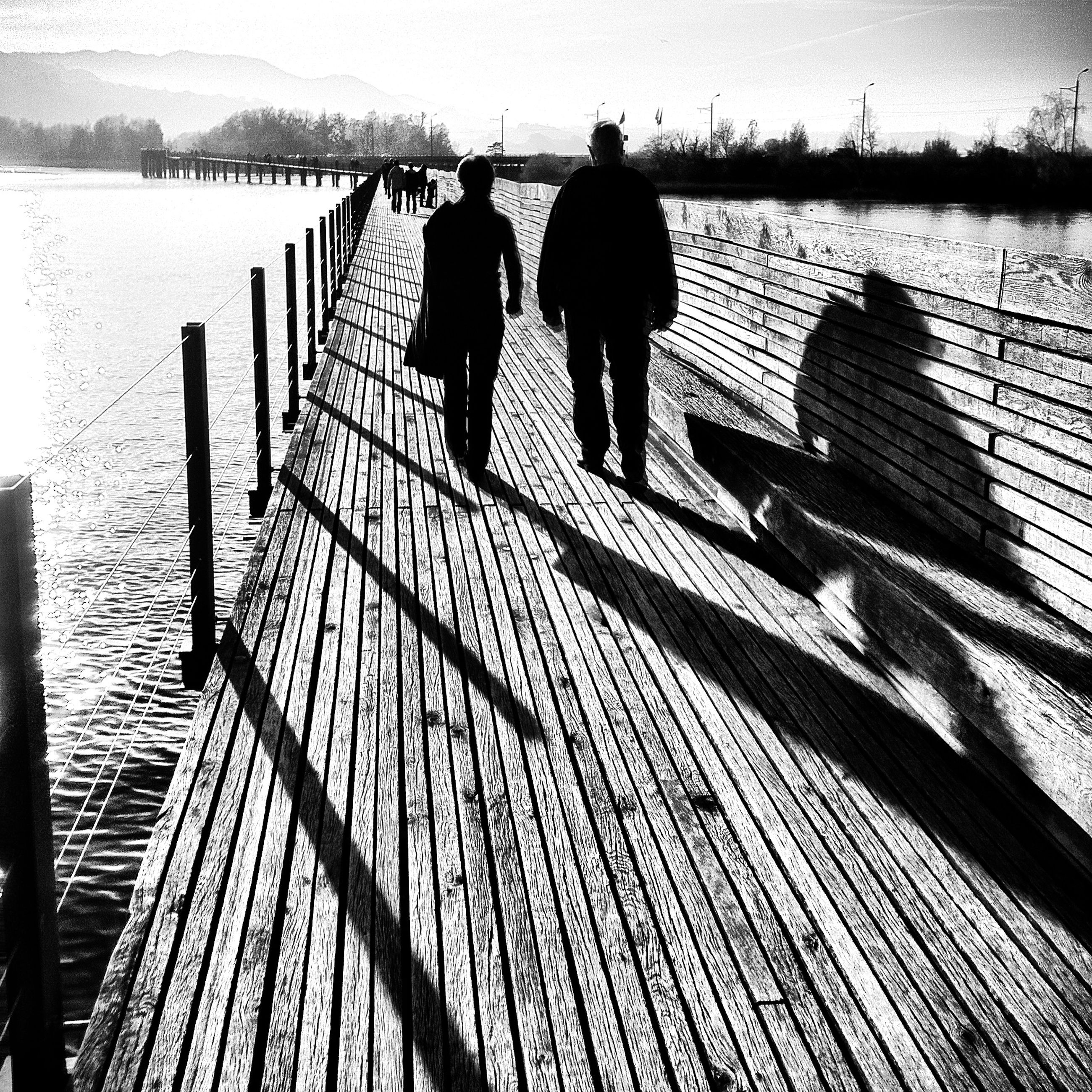 water, men, walking, railing, lifestyles, silhouette, leisure activity, full length, shadow, togetherness, rear view, sea, standing, person, reflection, pier, sunlight