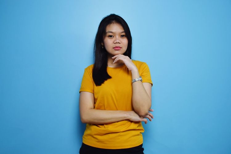 Beautiful young woman standing against blue background