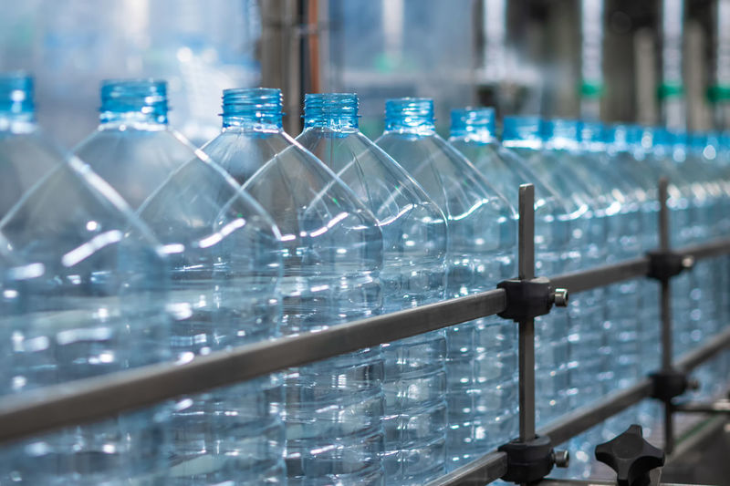 Empty blue five-liter plastic bottles on a conveyor belt. automated production of drinking water