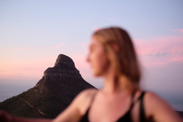 Close-up of woman against mountain during sunset