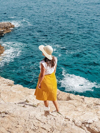 Young woman in yellow skirt standing on cliff above sea.